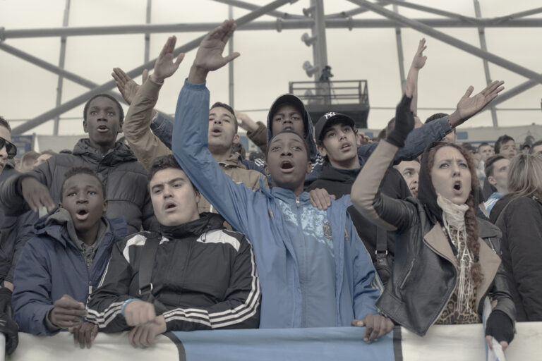 Supporters of the Olympic de Marseille soccer club, during a match into the Velodrome Stadium. Unlike other football fans, the Olympique supporters they travel around the country proclaiming their antiracist spirit and showing their pride of its multicultural identity. Marseille, department of Bouches-du-Rhône and region of Provence-Alpes-Cote d'Azur, France on January 17, 2014. Marseille is a city with enormous potential, it opens out onto the Mediterranean and it has the character of a cosmopolitan city with a young, multicultural population. This potential and the desire of the ruling class to give the city a new image, earned it the title of European Capital of Culture. The message emitted by the political organizations was clear. The year 2014 is crucial for Marseille. This is its opportunity to rid itself of the stigma of violence and crime that has hung over it, to move on from the social violence that pervades its streets and the obvious economic inequality. Under the label of Cultural Capital, earned after a financial investment of over 600 million euros, Marseille has experienced a huge urban transformation, with the main focus being the rehabilitation of the most emblematic areas and the creation of new cultural facilities in the old port. Today, with the cranes gone and the construction finished, the inhabitants of Marseille wake up with a bittersweet sensation, aware of how, despite initial promises, financial resources have been used to beautify chosen areas and collectives, leaving the disadvantaged neighborhoods totally excluded and accentuating the economic and socio-cultural contrasts.